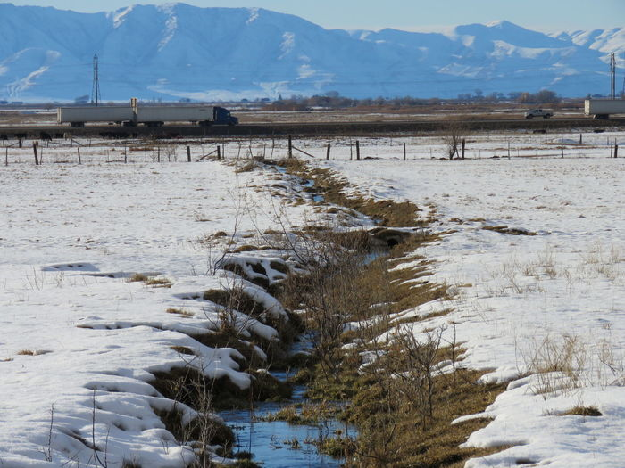 Stream on snow covered field against rocky mountains