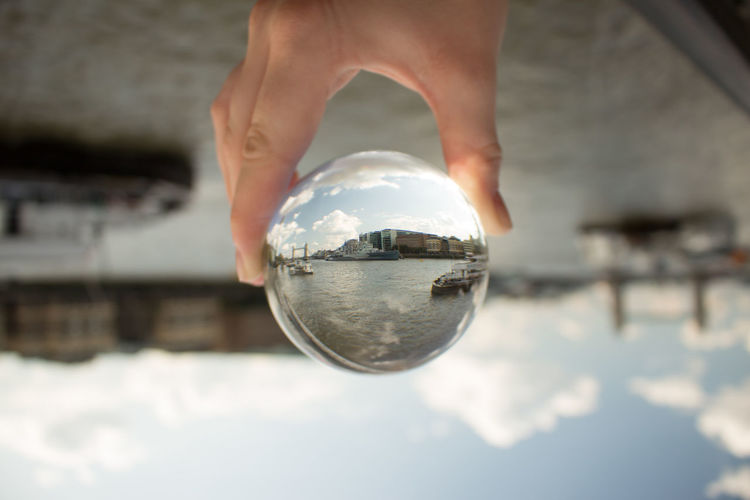 Close-up of hand holding crystal ball against lake