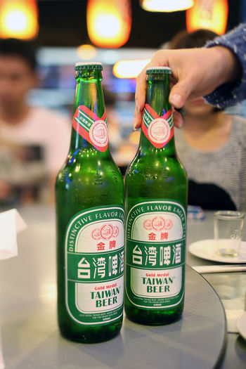 Taiwan Beer Container Drink Bottle Real People Refreshment Focus On Foreground Alcohol Leisure Activity Lifestyles Human Body Part Human Hand Table One Person Hand Close-up Indoors  Glass - Material Incidental People Business Glass Finger Taiwan Beer