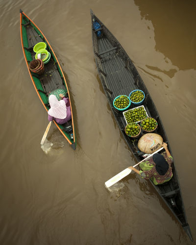 A View of Lokbaintan Floating Market traders with their traditional boat called Jukung. High Angle View Nautical Vessel Water Mode Of Transportation Transportation Occupation Real People One Person Day Men Nature Outdoors Oar Waterfront River Adult Moored Fisherman