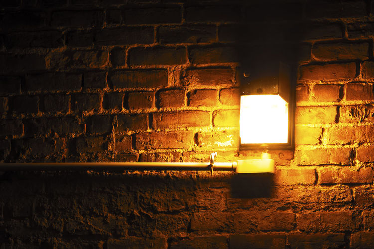 Illuminated lamp against brick wall