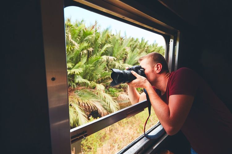 Young traveler on the holiday. Photographer with dslr camera photoshooting from open window of the vintage train. Adventure Camera - Photographic Equipment Enjoying Life Exploring Journey Journeyphotography Jungle Lifestyles Man Nature Passenger Photographer Photographing Photography Photography Themes Railway Skill  Technology Train Transportation Travel Traveler Traveling Trip Window