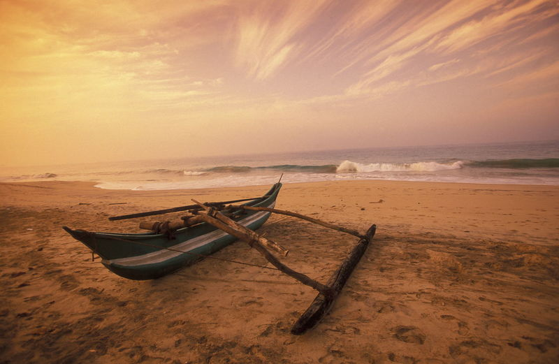 Abandoned outrigger canoe on beach against sky