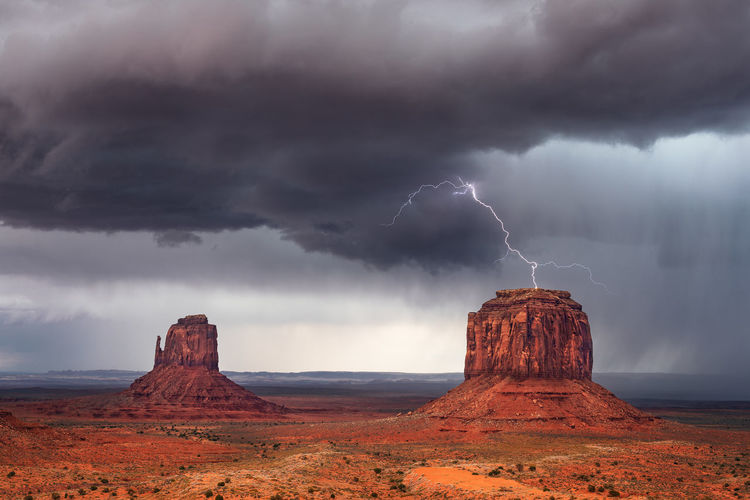 Scenic view of lightning over rocks against cloudy sky