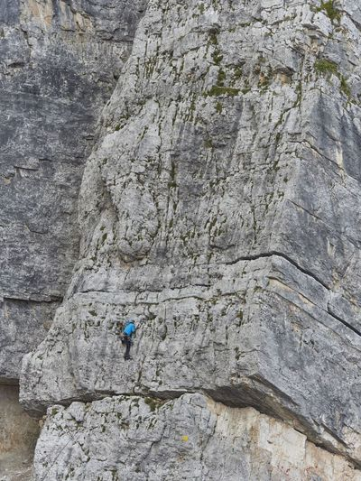 Low angle view of man climbing huge rock