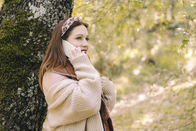 Portrait of beautiful young woman standing against trees in winter