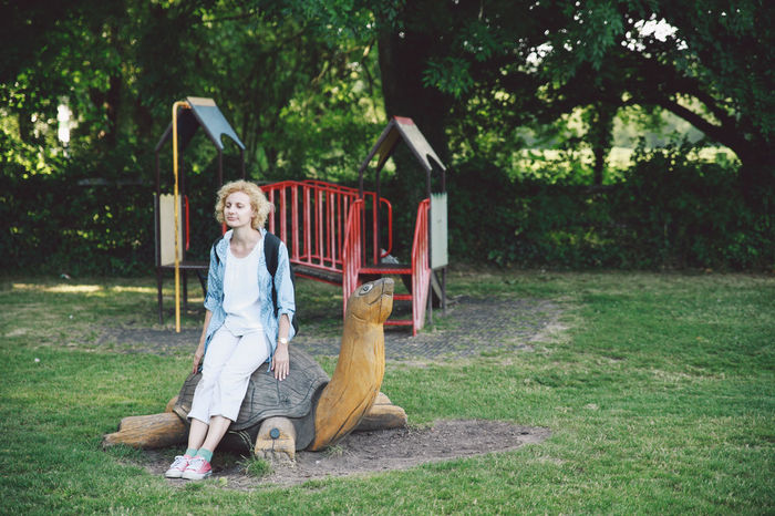Blonde Casual Clothing Children Playground Curly Natural Light Portrait Full Length Fun Girl Grass Grassy Green Color Growth Hair Leisure Activity Lifestyles Nature Outdoors Park Portrait Resting Summer Sunset Tree Tree Trunk Wood Turtle