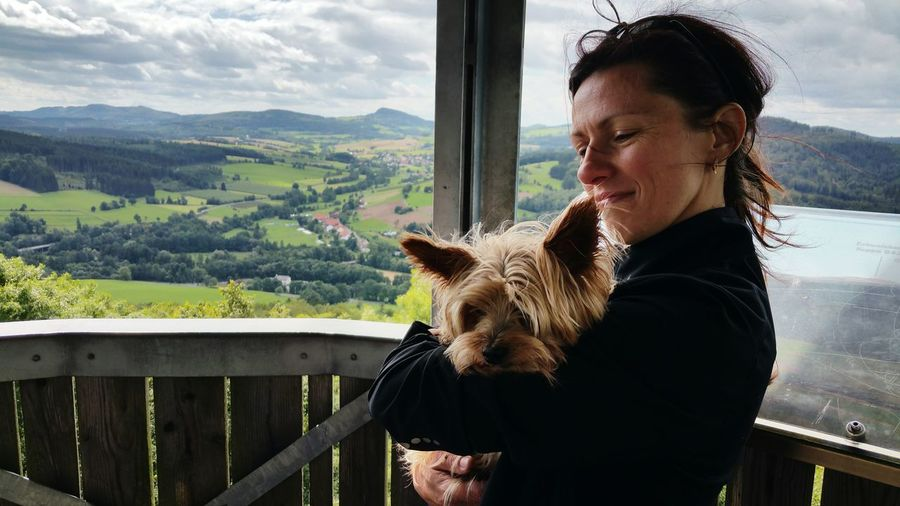 Close-Up Of Mature Woman Holding Dog While Standing At Observation Point
