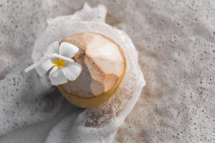 Exotic summer fresh coconut cocktail with flower on a sandy beach Coconut Coctails Drinks Exotic Holiday Beach Bevarage Food And Drink Freshness High Angle View No People Still Life Summer Tropical