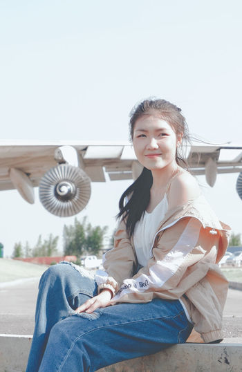 Portrait of smiling young woman sitting against sky