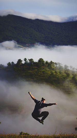 Woman climbing on mountain against sky