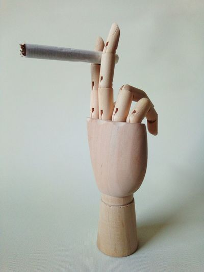 Close-up of wooden figurine holding cigarette against white background