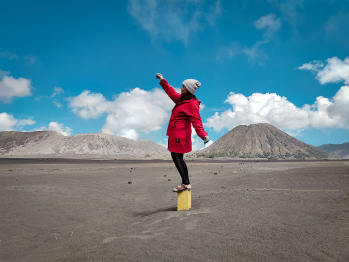 Full length of girl standing on land against sky