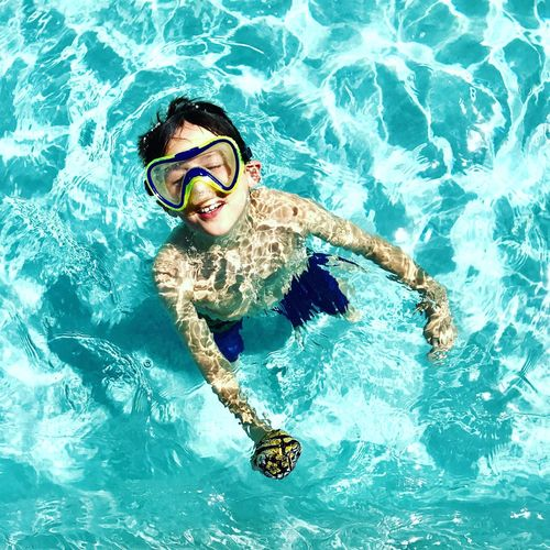 High angle view of boy wearing swimming goggles standing in pool
