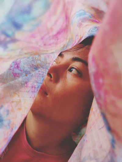 Close-up of young woman looking away seen through blanket
