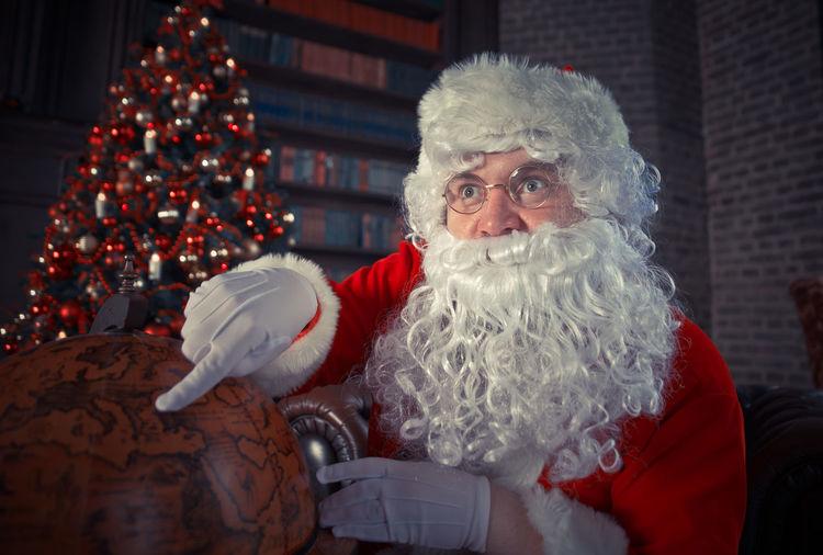 Man wearing santa claus costume pointing at globe at home