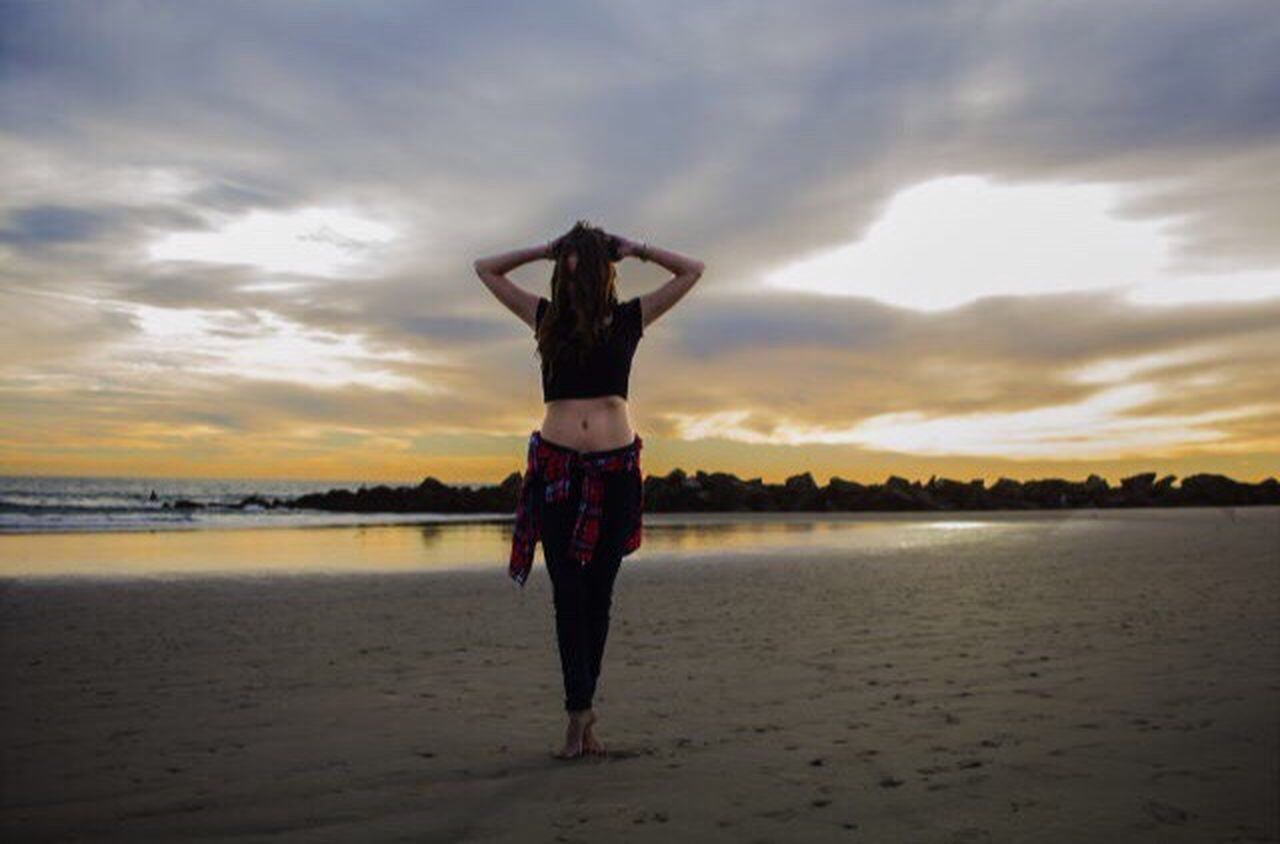 cloud - sky, sky, beach, sunset, full length, human arm, standing, outdoors, one woman only, one person, adults only, sea, adult, people, nature, horizon over water, young adult, one young woman only, human body part, only women, performance, water, day