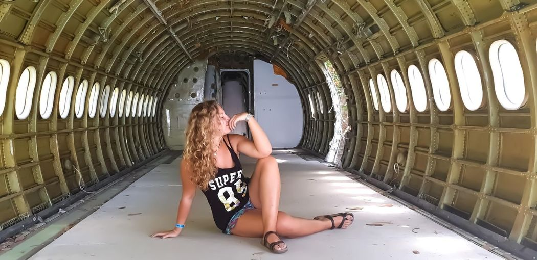 Full length of young woman sitting in abandoned airplane