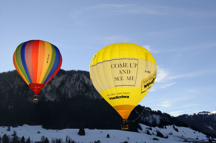 Chateaux d'Oex Chateaux D'Oex Colors Heißluftballon Pays D'En Haut Adventure Balloon Ballooning Festival Clear Sky Cold Temperature Day Farbenspiel Flying Hot Air Balloon Leisure Activity Mountain Multi Colored Nature No People Outdoors Parachute Sky Snow Transportation Winter Yellow