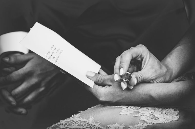 Midsection of bride holding ring and paper with text while sitting by groom