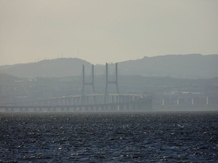 Bridge Over Sea By Mountains Against Clear Sky