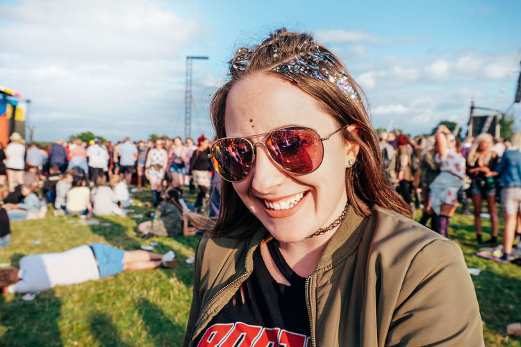 Portrait of smiling young woman wearing sunglasses in music festival