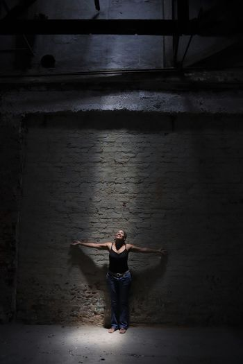 Mature Woman With Arms Outstretched Standing Against Wall