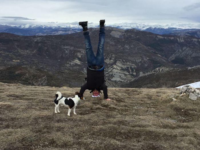 Full length of senior man doing headstand on mountain against cloudy sky