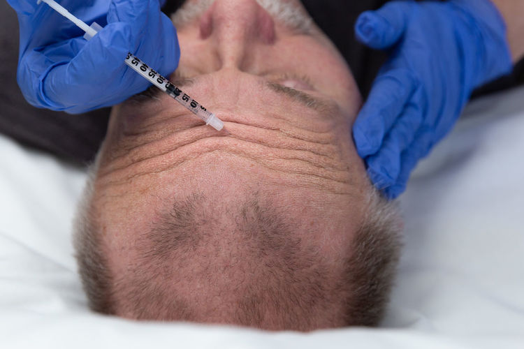 Cropped hands of doctor injecting on man face