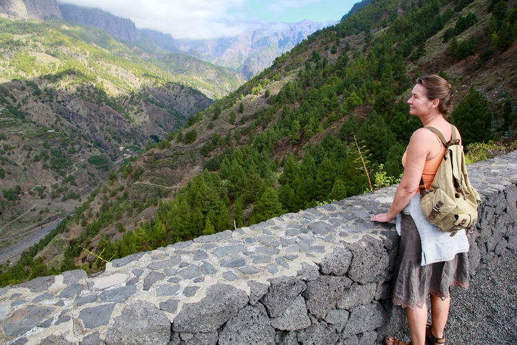 Full length of woman with arms raised on mountains