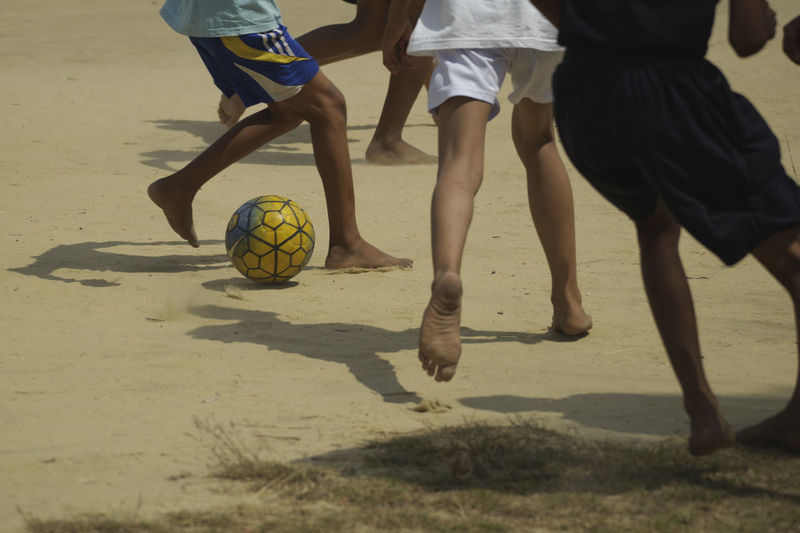 Low Section Of Boys Playing Soccer At Beach