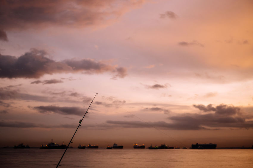 Fishing pole under warm-colored sky in front of sea Sky Cloud - Sky Sunset Beauty In Nature Water Scenics - Nature Sea Tranquility Nature Tranquil Scene No People Orange Color Silhouette Dramatic Sky Waterfront Outdoors Recreation  Relaxation Hobby Lifestyles Evening Morning Warm Colors