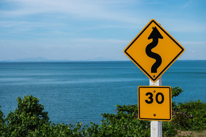 Traffic sign indicating a winding road must be using a speed of 30 kilometers per hour. Alarm Alertness Beware Careful Caution Communication Connection Direction Law Limit Nature Number Ocean Outdoors Road Sign Scenics Sea Signage Speed Limit Sign Traffic Water Yellow
