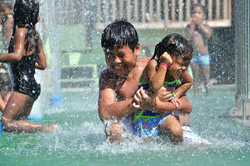 Children playing in swimming pool at water park