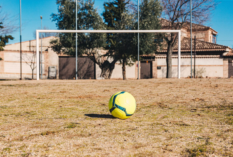 Soccer ball on field against trees