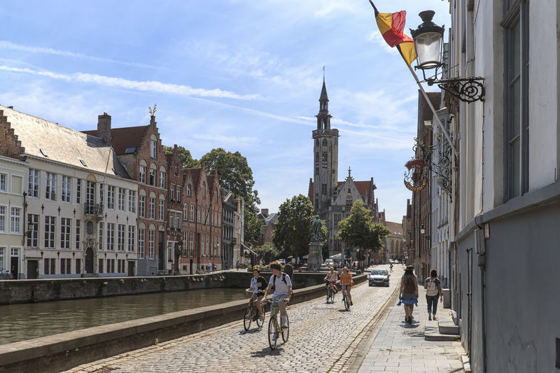 Bruges, Belgium - July 7, 2017: Tourists riding bikes on the streets of Bruges, Flanders in Belgium Beer Belgium Brugge Chocolate Dijver Canal Duvel Flanders Panoramic View Provinciaal Hof West Flanders Aerial View Belfry Tower Bikes Bruges Europe Flower French Fries Holland Market Square Medieval Town Mussels