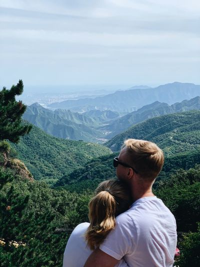 Rear view of couple embracing by mountains against sky
