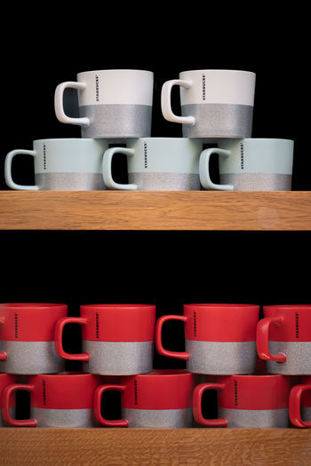 Coffee cup on table against black background