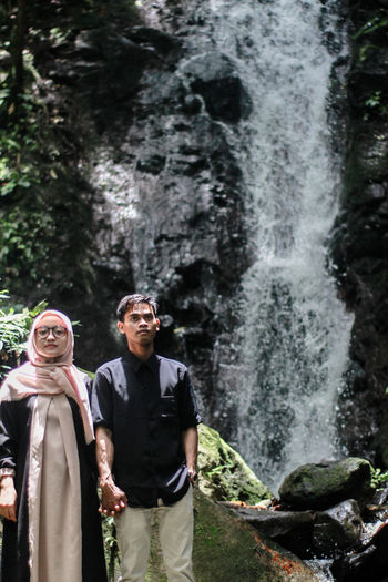 Couple looking away while standing against waterfall