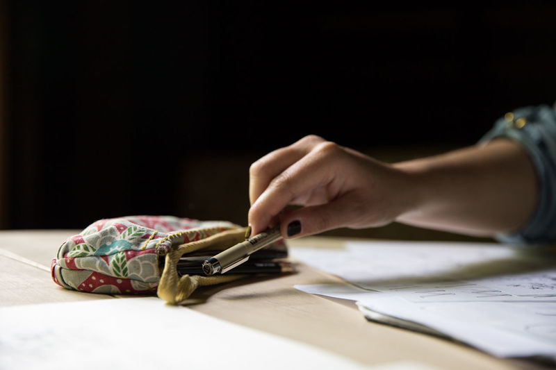 Cropped image of woman holding pen by pencil case at table