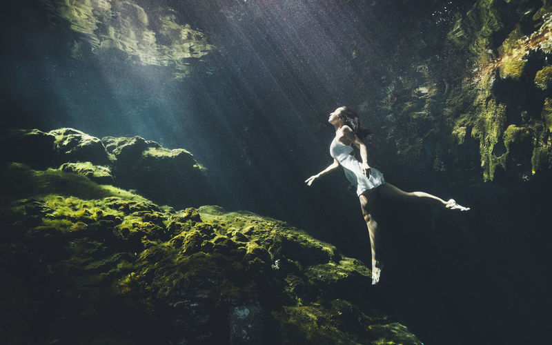 Woman underwater by rock formation