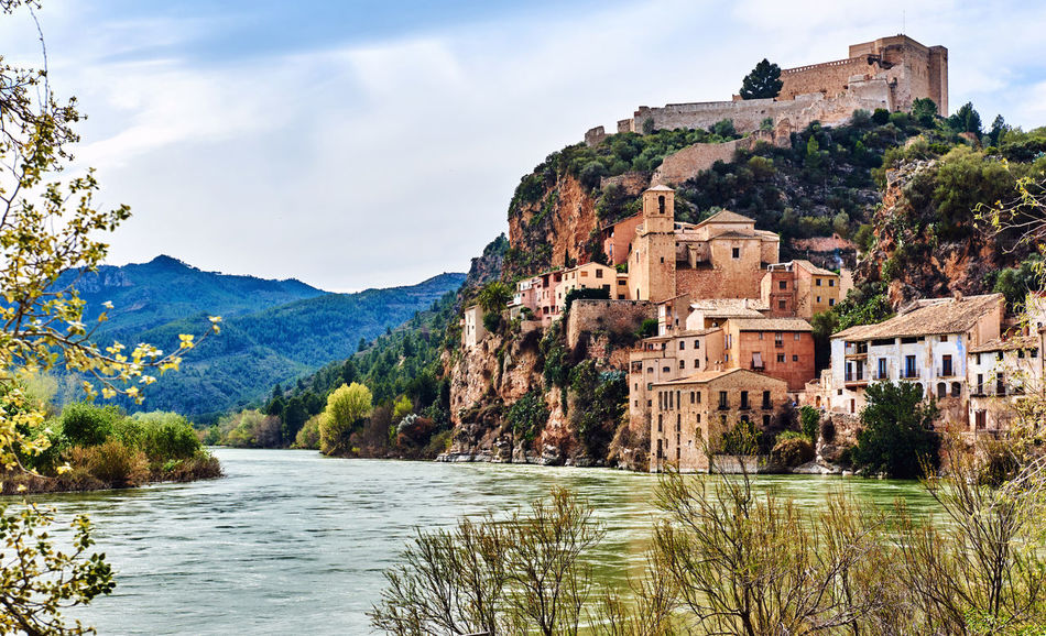 Miravet village and Ebro river. Province of Tarragona. Spain. Miravet is one of the most charming village in Catalonia Ancient Architecture Castle Catalonia Cloudy Sky Coastal Ebre River Europe Fortification Hillside Hilltop History Landmark Landscape Medieval Architecture Miravet, Spain Nature Old Town Picturesque Village Scenery SPAIN Sunny Day Tarragona Travel Travel Destinations Village