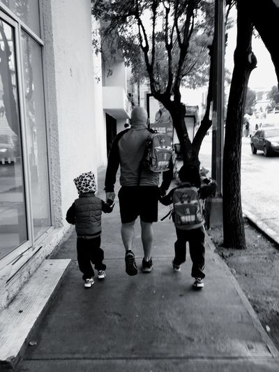 Rear view of father and kids walking on sidewalk