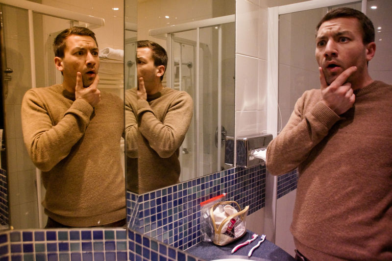 Shocked man standing by mirror in bathroom