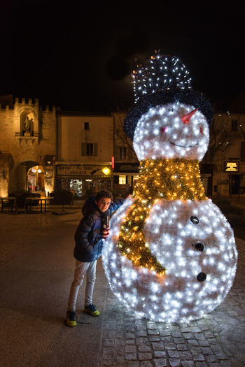 Snowman Christmas Decoration Christmas Christmas Lights Christmas Ornament Childhood Child One Boy Only One Person Children Illuminated Architecture Night Full Length Building Exterior Built Structure Standing Real People Celebration Men Glowing City Decoration Building Holiday Lifestyles Leisure Activity Outdoors Warm Clothing Friend