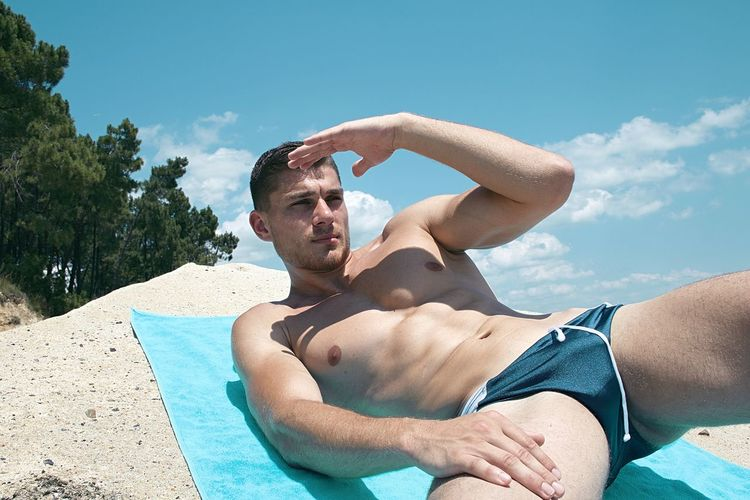 Midsection of shirtless man in swimming pool against sky