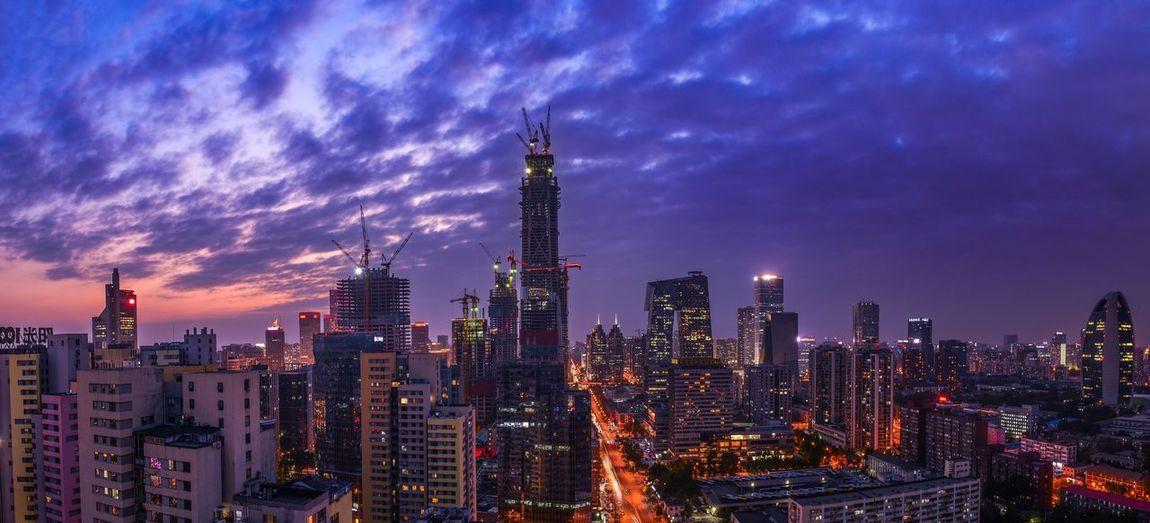 Illuminated cityscape against cloudy sky during dusk