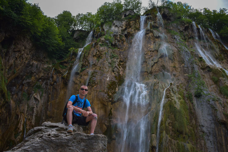 Low angle portrait of young man wearing sunglasses sitting on rock against waterfall