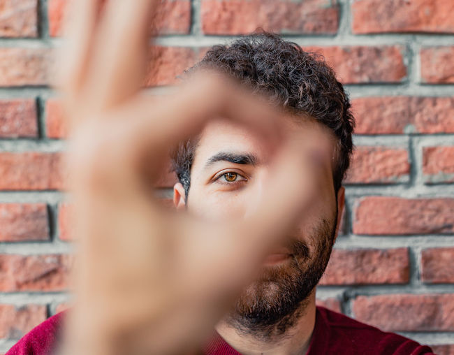 Close-up portrait of man gesturing ok sign against brick wall
