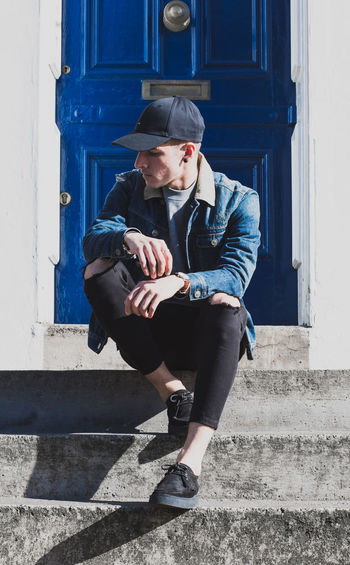 man sitting in front of door in grunge, urban fashion. Adult Adults Only Blue City Cool Day Door, Fashion Flat Cap Full Length Headwear Lifestyles One Man Only One Person Only Men Outdoors People Sitting Social Issues Stairs Stairs_collection Urban Urbanphotography Young Adult